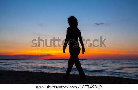 young woman walking on the beach at sunset - stock photo