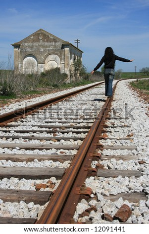 Young woman walking on the railway of an abandoned train station. - stock photo