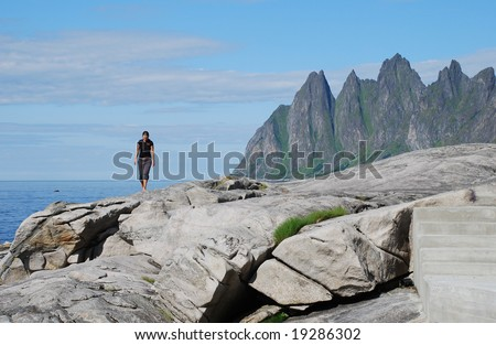 Young woman walking on the rocks by the sea