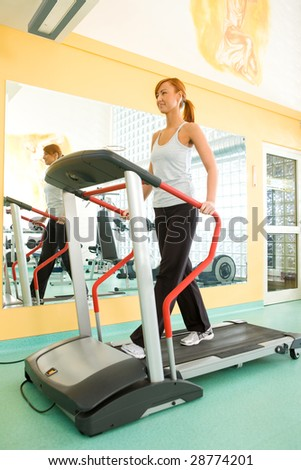 Young woman walking on treadmill at gym.