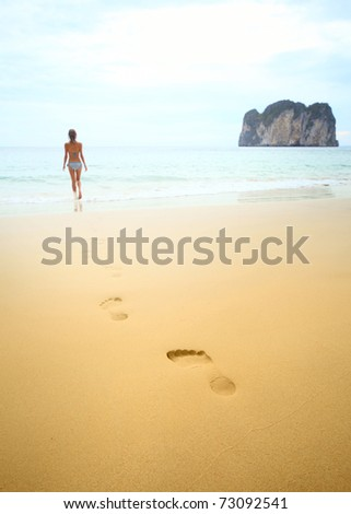 Young woman walking on wet perfect sand and going to swim in a sea - stock photo