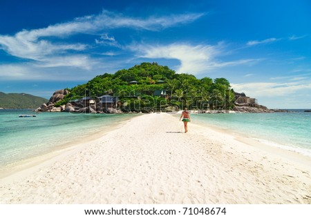 Young woman walking per sand spit to tropical island