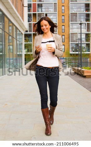 young woman walking sending a message and drinking coffee - stock photo