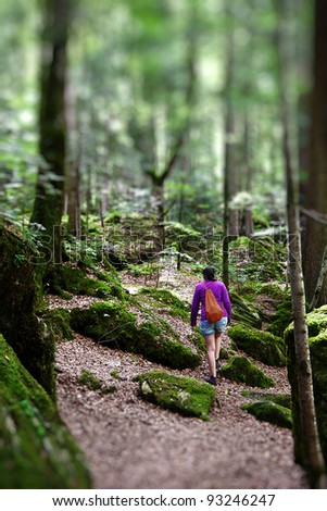Young woman walking through a deep forest - stock photo