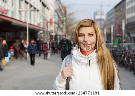 young woman walking through crowded pedestrian street lined with shops - stock photo