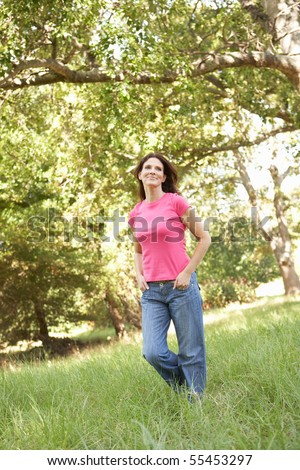 Young Woman Walking Through Long Grass In Park
