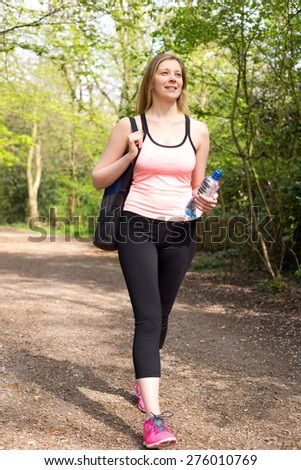 young woman walking through the park after exercise
