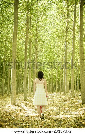 Young woman walking through the woods. - stock photo
