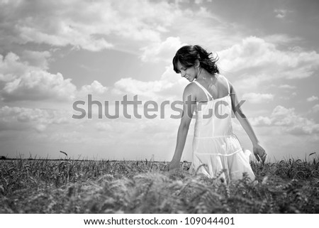 Young woman walking through wheat field touching wheat, black and white