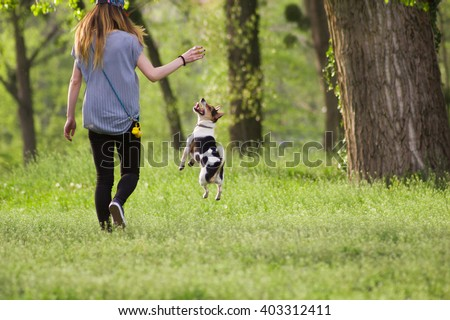 Young woman walking with a dog playing training, jumping dog