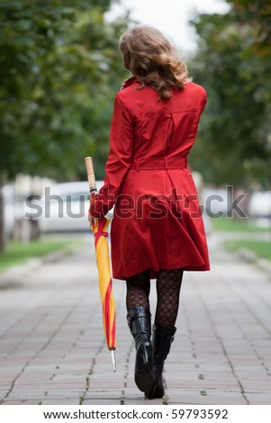 young woman walking with an umbrella - stock photo