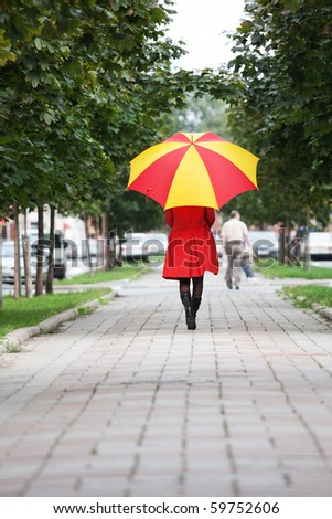young woman walking with an umbrella in the rain - stock photo