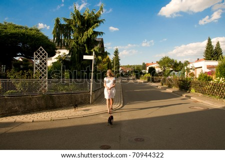 Young woman walking with her two small dogs.