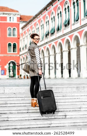 Young woman walking with travel bag up stairs at the Republic square in Split city - stock photo