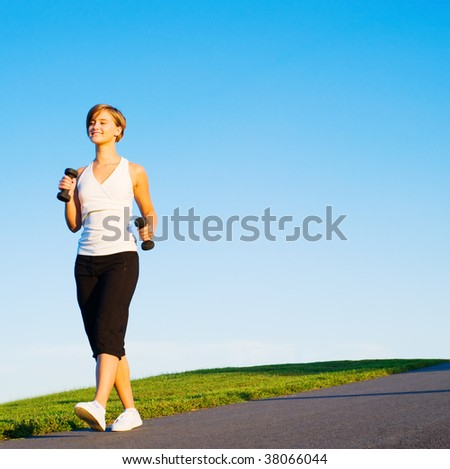 Young woman walking with weights, from a complete series of photos.