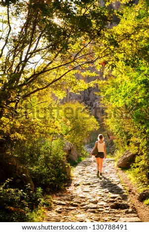 Young woman walks down a rocky trail in Velebit national park, Croatia, at sunset - stock photo