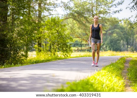 Young woman walks outdoor and listens to music - stock photo