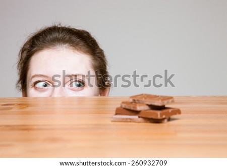 Young woman wanting to eat milk chocolate, neutral background - stock photo