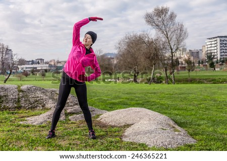 Young woman warming up and stretching the upper body and arms before running on a cold winter day in an urban park. - stock photo