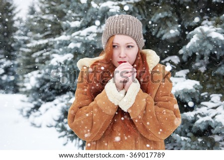 Young woman warms hands at winter, snowy fir trees background - stock photo
