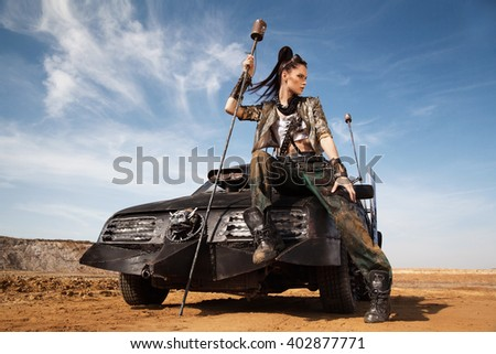 Young woman warrior in brutal futuristic style clothes with car - stock photo