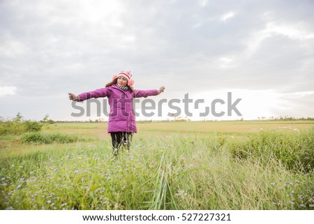 Young woman was playing in a field of flowers in the winter air.