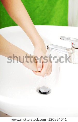 Young woman wash her hands - stock photo
