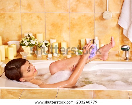 Young woman wash leg in bathtube. - stock photo