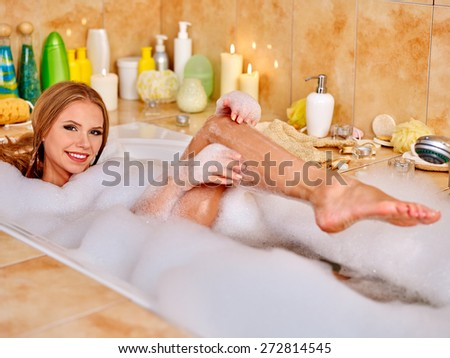 Young woman wash leg in bathtube. A lot of water. - stock photo