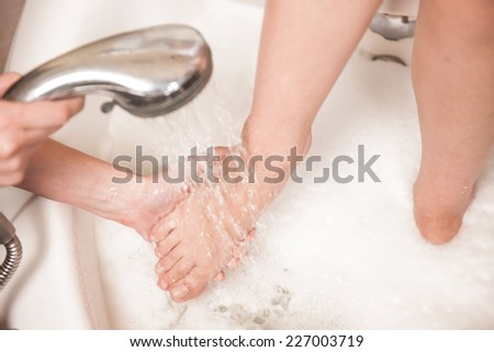young woman washes and cleans beautiful legs. closeup of beautiful feet care in spa  - stock photo