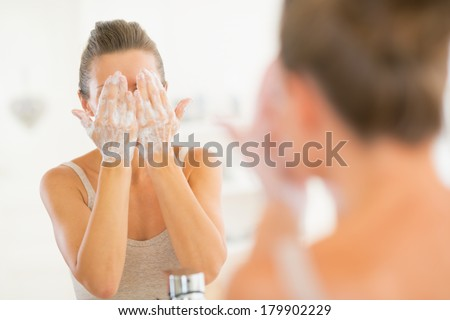 Young woman washing face in bathroom - stock photo