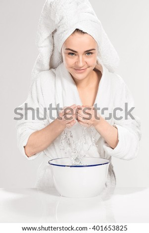 Young woman washing face with clean water - stock photo