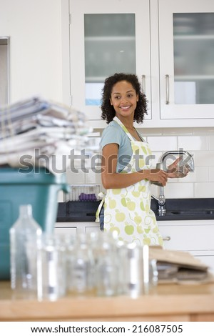 Young woman washing glass jar and can for recycling, smiling (differential focus) - stock photo