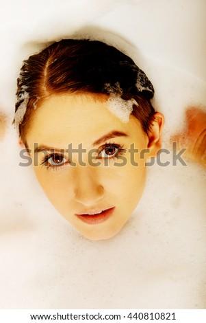 Young woman washing hair in bath - stock photo