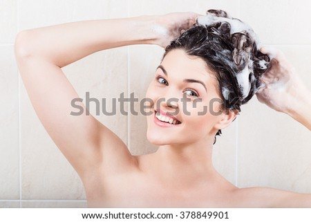 Young woman washing hair with shampoo in the shower - stock photo