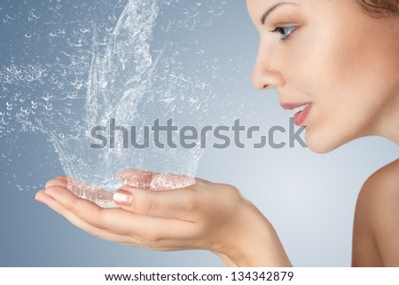 Young woman washing her face and hands with clean water in the morning - stock photo