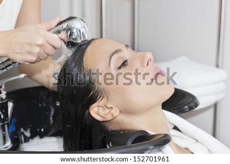 Young woman washing her hair in  the Hair salon.  - stock photo