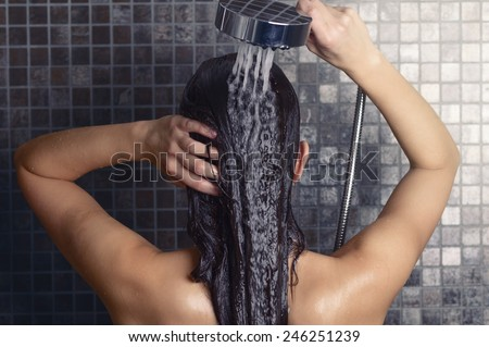 Young woman washing her long hair under the shower standing with her back to the camera rinsing it off under the jet of water with her head partially turned to the side, over grey mosaic tiles - stock photo