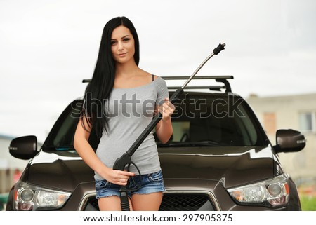 Young woman washing the car smiling.