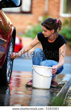Young woman washing the wheel of a red car - stock photo