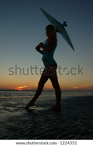 Young woman watches sunset under a parasol silhouette