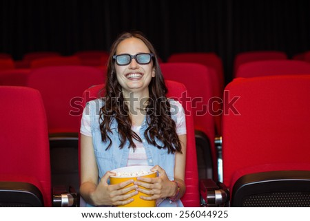 Young woman watching a 3d film at the cinema - stock photo