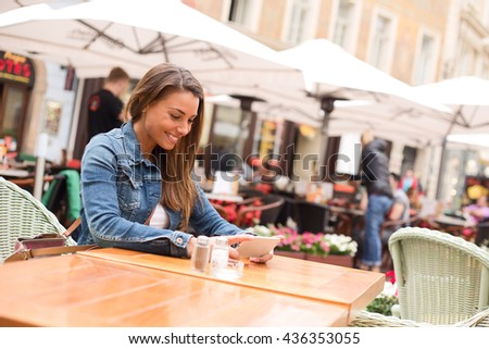 young woman watching a film on her phone at a restaurant - stock photo