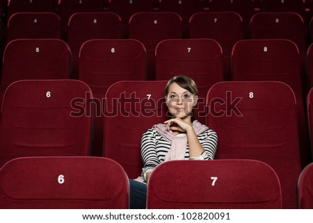 Young woman watching a movie alone - stock photo