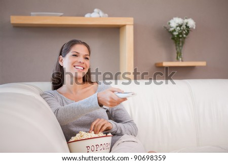 Young woman watching a movie with a bowl of popcorn - stock photo