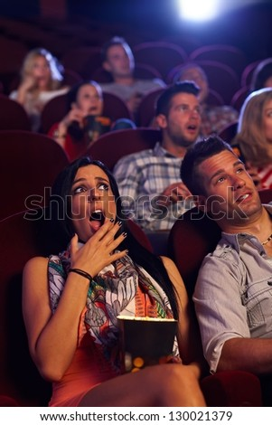 Young woman watching horror movie at cinema, looking shocked, holding popcorn in hand. - stock photo