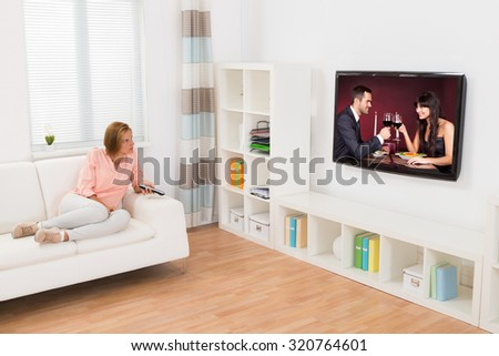 Young Woman Watching Movie On Television In Living Room