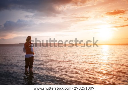 young woman watching sea sunrise