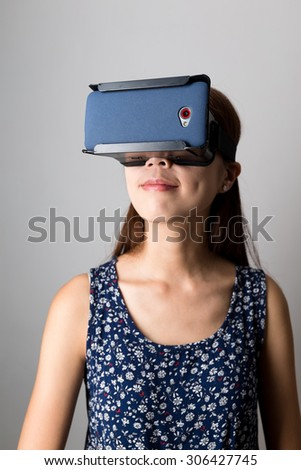 Young Woman watching the film with virtual reality device - stock photo