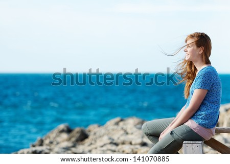 Young woman watching the ocean sitting on a wooden railing above a rocky shoreline with a lovely smile - stock photo
